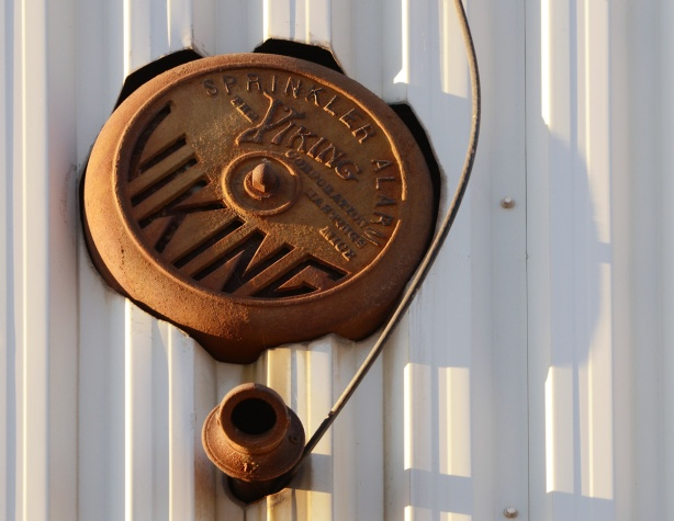 an old round rusty Viking brand sprinkler alarm on the outside of a building