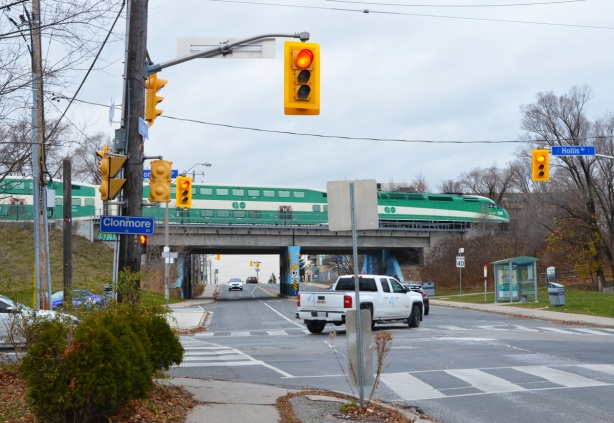 a white pickup truck makes a turn at an intersection with a GO train going over a bridge in the background