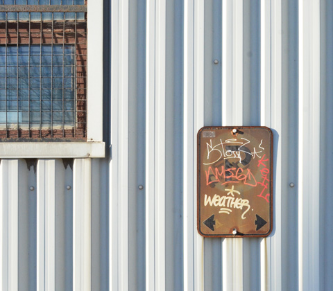 corrugated metal cladding on a building with a window and an old rusty sign with graffiti on it