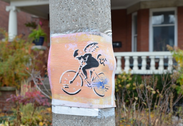 stencil on paper on a utility pole, in orange and black, a girl riding a bike, with wings on her back