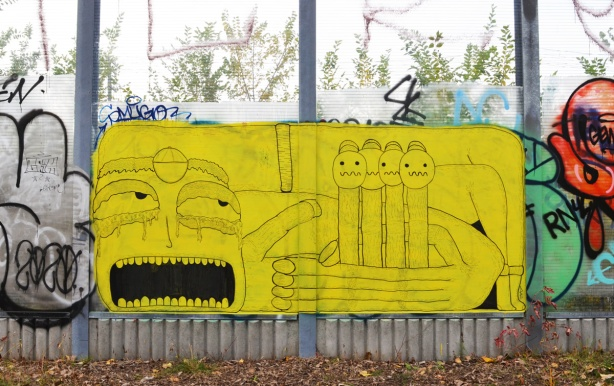 yellow street art painted on glass wall beside West Toronto Railpath and railway tracks, large face with mouth open, hand holding 4 little figures that look like fingers