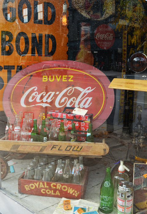 items in a store window, vintage, old coca-cola sign and other memorabilia, also Royal Crown Cola bottles and wood box, a wood Flow wagon,