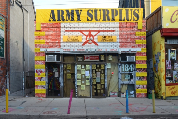 front of yellow painted store, army surplus store in Kensington, lots of little signs in the window,