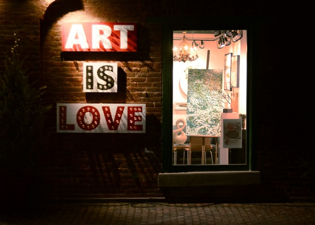evening photo, distillery district, decorated for Christmas, the words art is love in big block letters, outside the window of an art gallery with a painting in the window