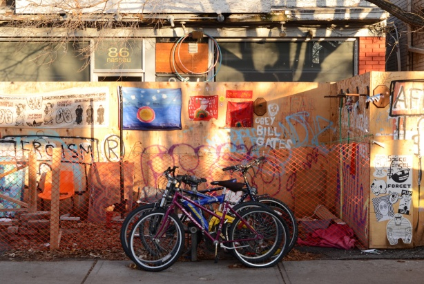 bikes locked in front of a plywood makeshift fence around an empty storefront at 86 Nassau street in Kensington, signs and graffiti on the fence, artwork, protest