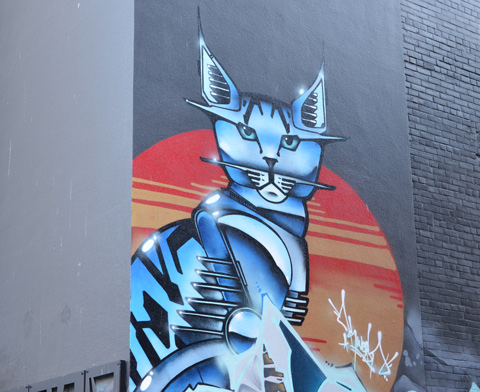 mural of a blue cat in front of the orange-ish rising sun (or setting sun?)