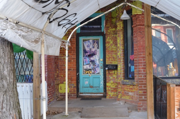 turquoise door with window it. window is covered with pictures, entrance to store is small sidewalk that is covered with a temporary portable tent like structure,