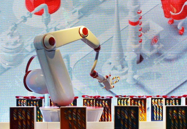 a shiny white robotic arm packages candy canes into boxes, an h b c window display, striped candy canes,