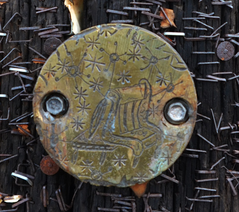 small brass coloured circle with carvings on it, attached to wood utility pole among hundreds of old staples