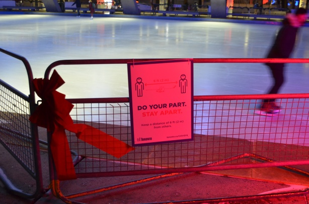 red flood lit metal barricade beside rink at Nathan Phllips Square, with a big red bow on it as well as a sign that says do your part, stay 2 metres apart, covid sign