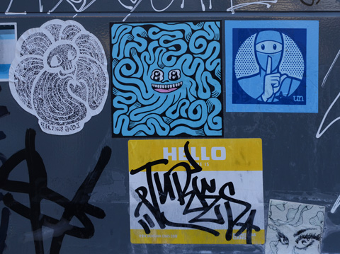 stickers on a grey metal box, feelings bot, tbonez, a drawing of a womans face