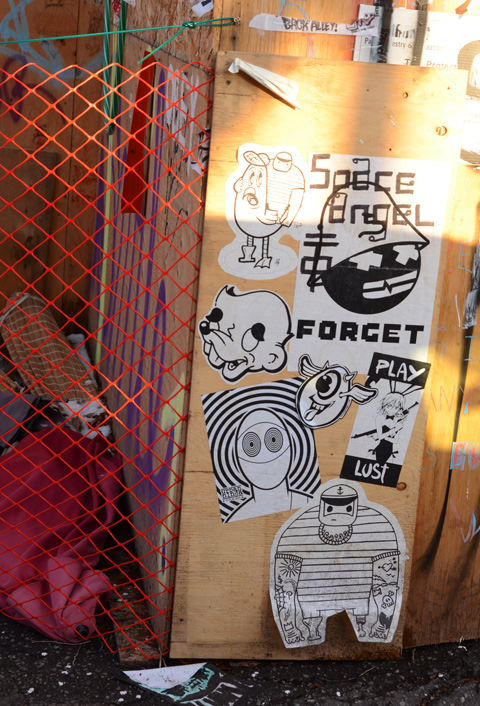 black and white posters and slaps graffiti on a plywood fence, urban ninja squadron, sketchrat, forget,