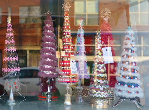 looking in a store window, little Christmas trees made in cone shapes with fuzzy and shiny items.