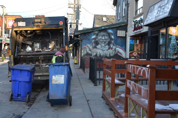 garbage man hauling blue bin towards back of truck, garbage day in Kensington, mural on the side of one of the stores, empty fenced in patios,