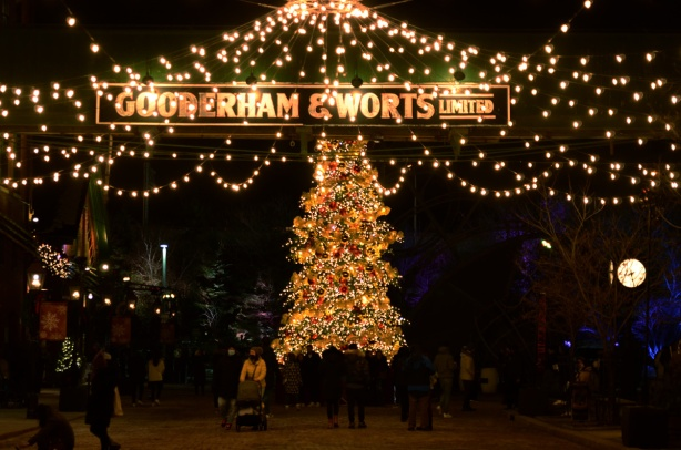 evening photo, distillery district, decorated for Christmas, large Christmas tree, sign Gooderham and worts over the road, strings of white lights