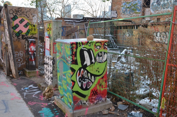 street art on metal boxes on sidewalk in front of a vacant lot with partially destroyed building on it
