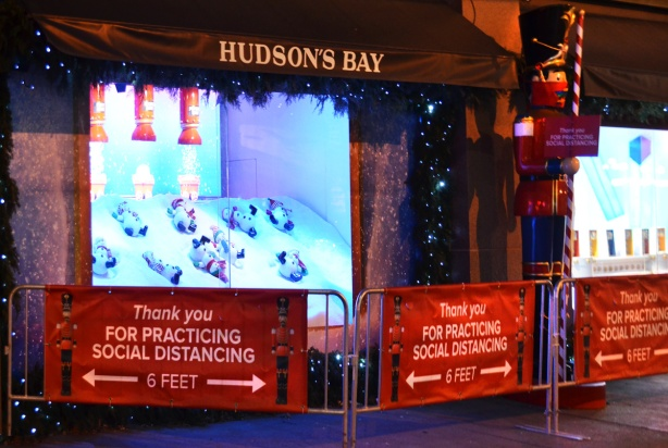 christmas light display in Hudson Bay store windows on Queen Street, barriers with signs saying don't forget to social distance