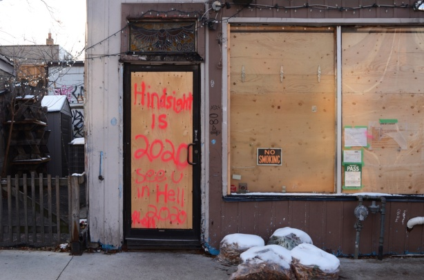 plywood over a glass door, with spray paint words that say hindsight is 20 20 see you in hell 2020.