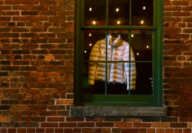 lights reflected in a window, green window frame, on old brick building, also a puffy winter jacket hanging in the window