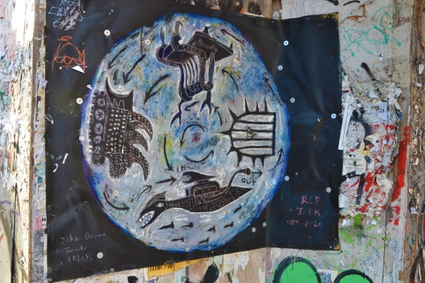 a painting tacked to construction hoardings, signed John Brown Toronto artist, on black paper, a circle with four main things inside it, first nations symbols