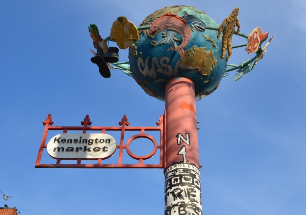 tall pole to mark Kensington market area of Toronto, with a globe on top. Circling the globe are objects like a shirt, a piece of meat, things that represent merchandise in the market