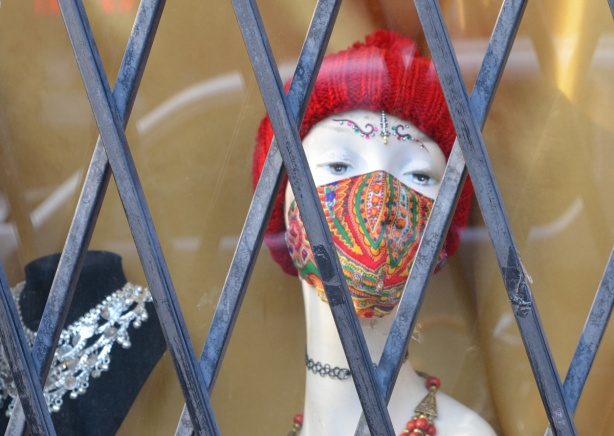 a head mannequin in a jewellry store window, with a red covid mask on