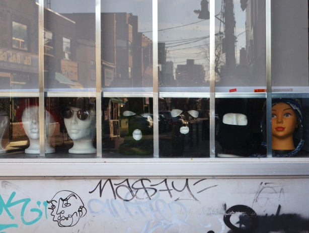 in a store window, at the bottom are 4 head mannequins with sunglasses and or black balaclavas on display
