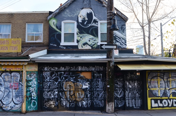 building covered with street art, two storeys, windows above, store below. Greys. panels covering store windows are all covered with painting too