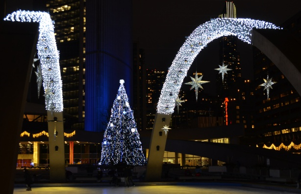 christmas lights and stars on the arches over the skating rink at Nathan Phillips square, with the large Christmas tree covered in blue and white lights behind. Also, part of the towers of city hall are lit blue