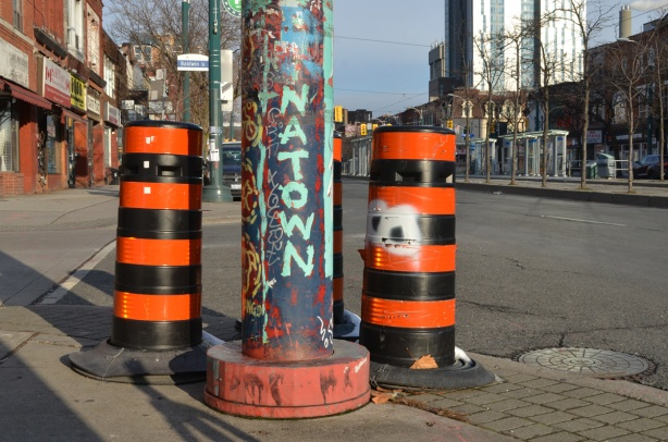 a metal post on Spadina with chinatown painted on it, 2 large black and orange traffic cones