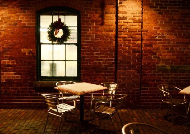 patio outside a restaurant window, wreath on window, snow on the table on the patio, metal table and chairs, old brick building in distillery district ,