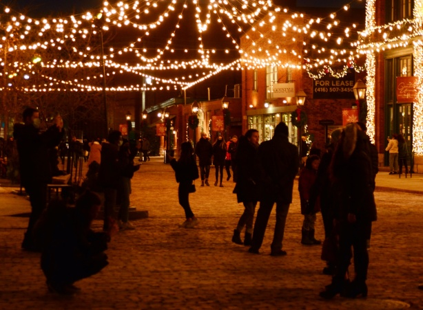 evening photo, distillery district, decorated for Christmas, people taking pictures, people walking