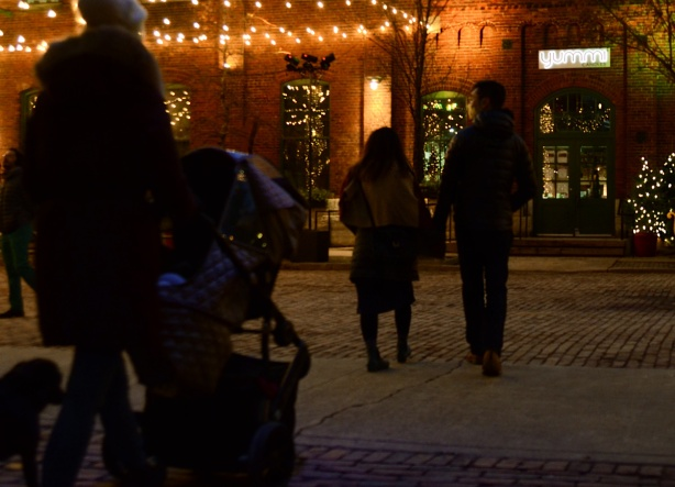evening photo, distillery district, decorated for Christmas, a couple walking, a woman pushing a stroller
