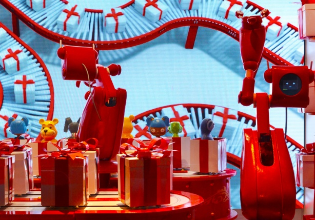 one of the H B C windows, shiny red robots pack toys into white boxes with red ribbons, production line,