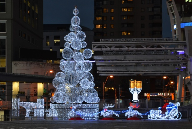 light display at Yonge Dundas square, a tree made of globe shapes, santa in his sleight, a hanakah menorah,