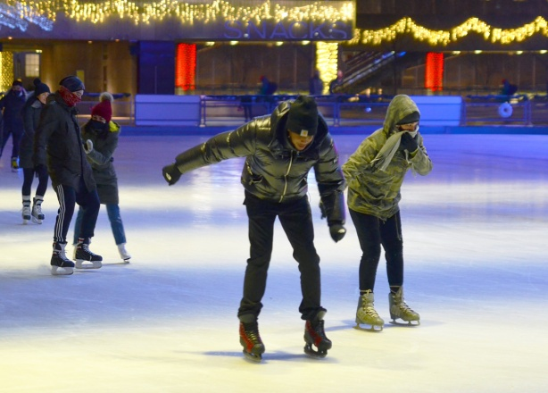 a young couple learning to skate together at Nathan Phillips, after dark, holding hands, hesitant but upright