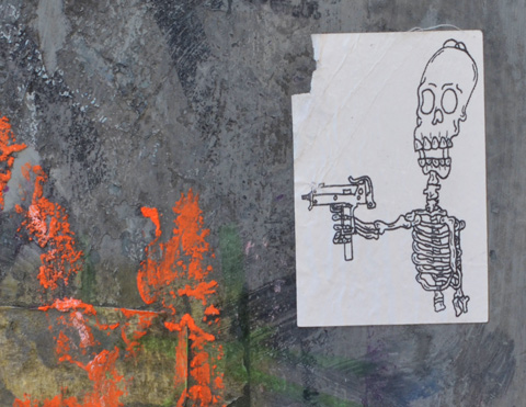 small stciker on a metal box, a skeleton is pointing a gun