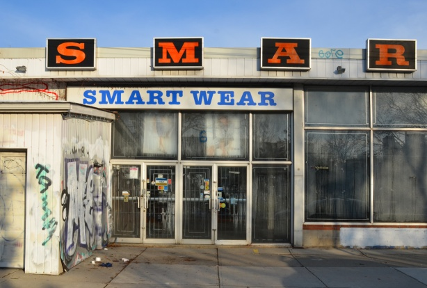 front of old smartwear store, now closed and empty, very dirty glass on windows and doors