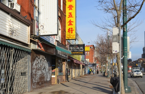 storefronts on Spadina ave., a large yellow sign with red chinese characters for Tap Phong trading company, empty sign, storefront with metal gate covering entrance,