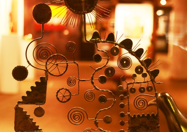 metal sculpture in a window, made with metal wire, many spiral shapes