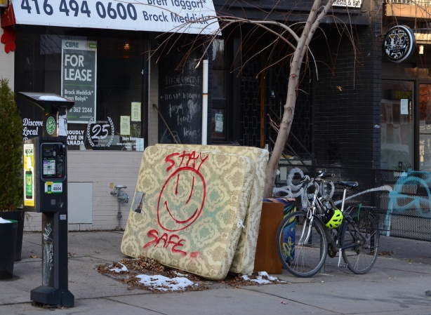2 old mattresses left on the sidewalk, leaning against a small tree. big happy face spray painted onto one of them along with the message stay safe
