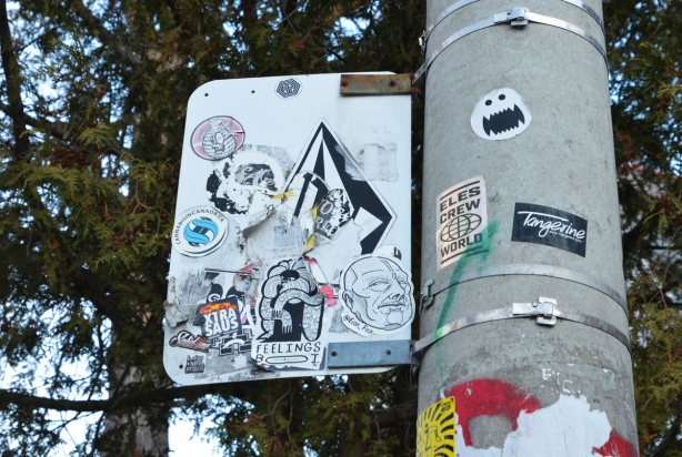 graffiti stickers on the back of a street sign