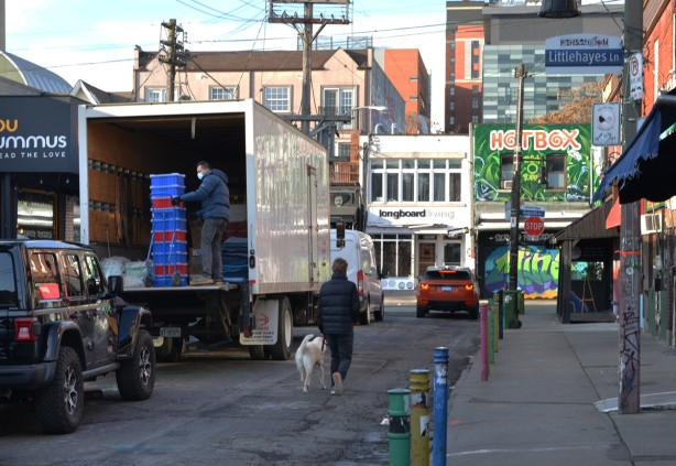 a man walks his dog along the street past the back of a truck where another man is unloading