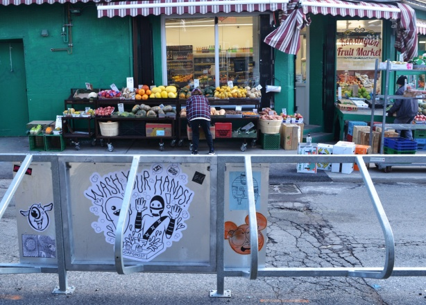 across the street, people are getting a fruit and vegetable store ready to open up, putting food on display outside. in the foreground is a metal bike stand with graffiti slaps on it, including a urban ninja squadron and soap ghost, wash your hands