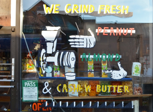 paintings on the glass on the window of a store, we grind fresh, peanuts, almonds, picture of a hand and a grinder