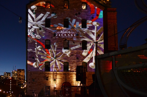 evening photo, distillery district, decorated for Christmas, large snowflakes projected onto the side of an old stone building