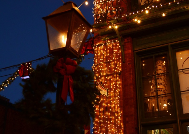 evening photo, distillery district, decorated for Christmas, a street lamp that looks like an old gas lamp, with a wreath and a big red bow, beside a mens wear store with a picture of the Leaning Tower of Pisa in it