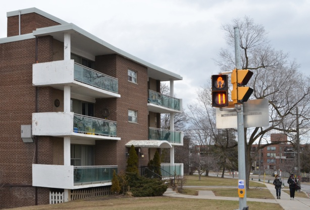 three storey red brick apartment building on the corner of Don Mills and the Donway with traffic light