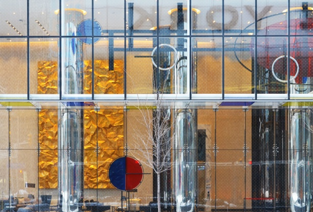 looking into the lobby of a condo building, through a large glass wall, some art inside including a large wall panel that looks like crinkled shiney gold paper, some reflections,