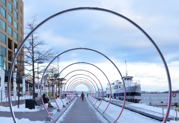 rings with a pinkish colour surround a walkway, a woman is walking through them, on the waterfront, a boat is docked beside the walkway